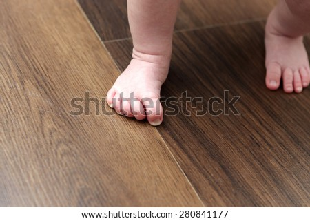 Pink baby feet on a wooden floor - stock photo