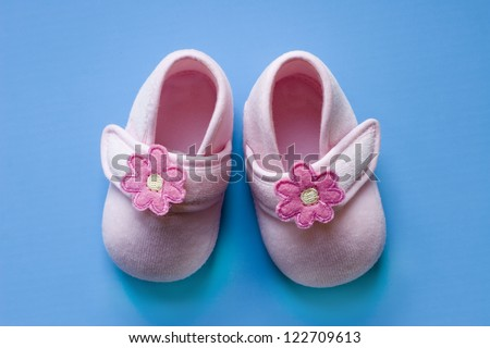 pink baby shoes on a colourful blue background - stock photo