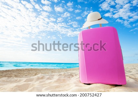 Pink baggage bag on the sand on the beach and women straw hat with white clouds sky - stock photo