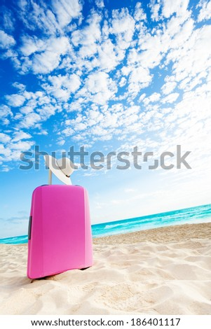Pink baggage bag on the sand on the beach with straw hat - stock photo