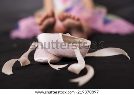 Pink ballerina baby shoes with girl feet in the background - stock photo