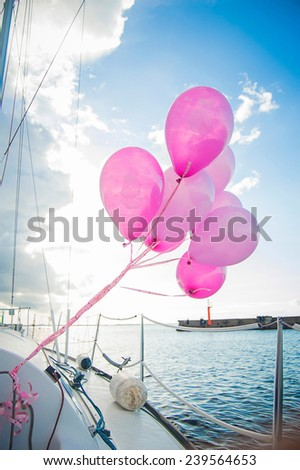 Pink balloons are waving in the wind on yacht in the sea at sunset - stock photo
