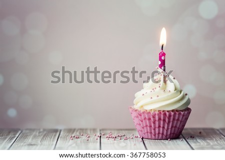 Pink birthday cupcake with candle - stock photo