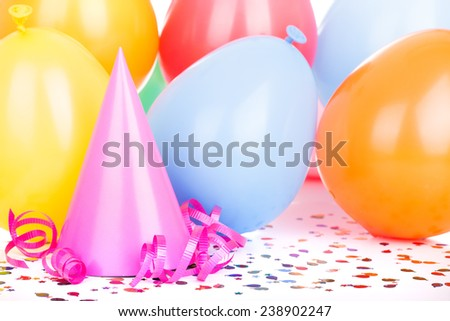 Pink birthday party hat with balloons in background - stock photo