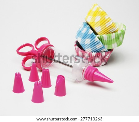 Pink blue green and yellow liners for cupcakes and decoration equipment in white background - stock photo