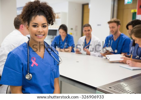 Pink breast cancer awareness ribbon against medical student smiling at the camera during class - stock photo
