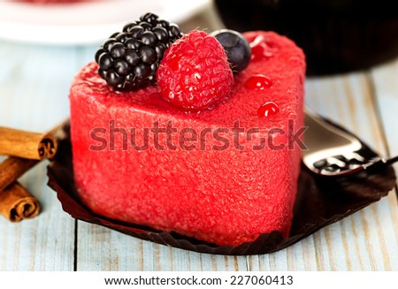 Pink cake with berries on wooden background - stock photo