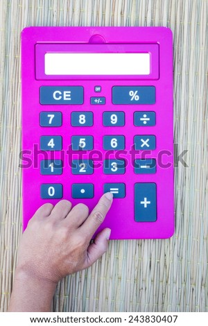 pink calculator on traditional mat with white space on the screen, hand pushing equal button, with white space on the screen - stock photo