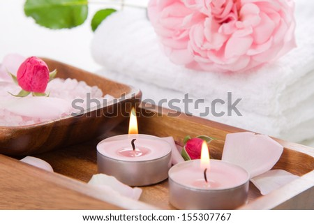 Pink candles and bath salt in wooden container - spa set in white and rose - stock photo