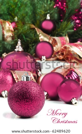 Pink christmas decorations under a christmas tree in low light with high contrast - stock photo