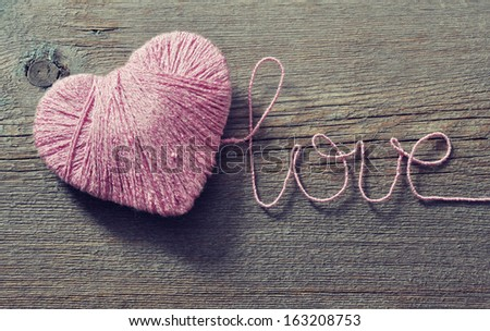 """Pink clew in shape of heart and word """"love""""on vintage wooden background - stock photo"""