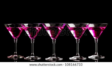 pink cocktails in martini glasses isolated on black - stock photo
