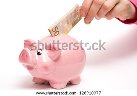 Pink coin bank as pig with fifty euro note in a female hand - stock photo