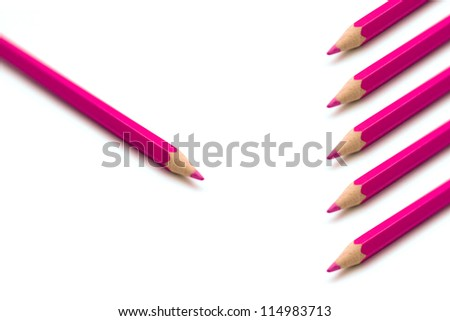 Pink colorful crayons in a row against one single crayon, group versus individual concept, marketing idea concept - stock photo