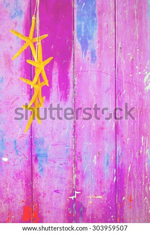 Pink colorful vintage background with shabby distressed grungy texture hippie style decorated with yellow sea stars hanging from a straw string.  - stock photo