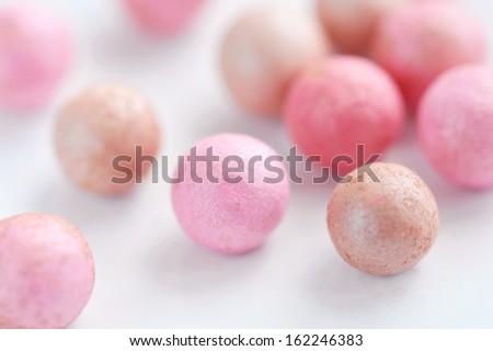 Pink cosmetics rouge balls on white, macro - stock photo