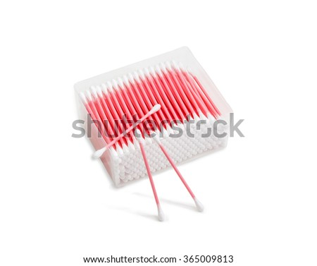 Pink cotton buds in plastic transparent rectangular container and several cotton buds separately on a light background