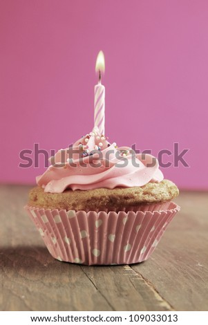 Pink cupcake with birthday candle on  wooden table - stock photo