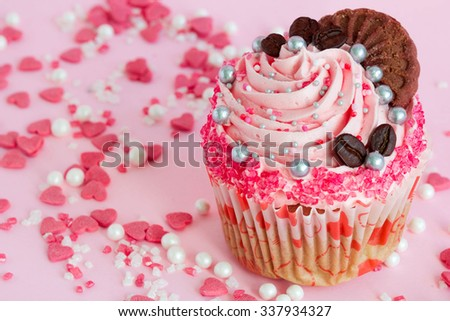 Pink cupcake with frosting and sprinkles around it. - stock photo