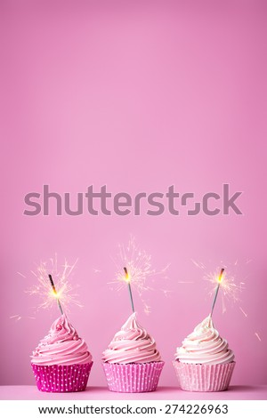 Pink cupcakes with sparklers and copy space above - stock photo