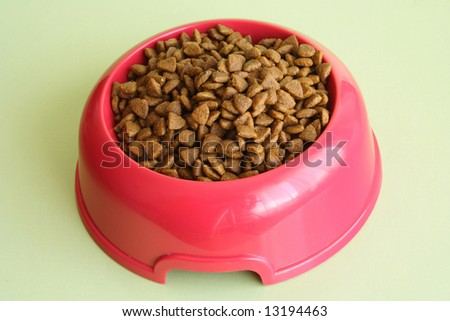 Pink dog bowl full of biscuits over green background - stock photo