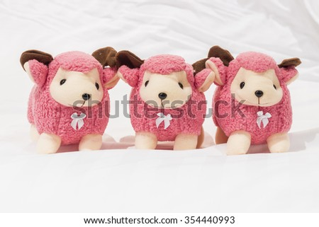 Pink Dolly the sheep lay in bed. - stock photo