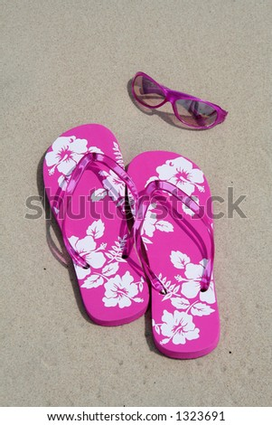 Pink flip-flops and sun glasses on the sand at the beach - stock photo