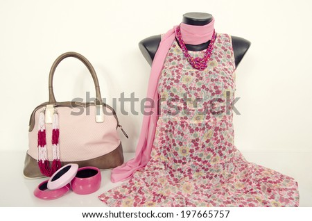 Pink floral dress on mannequin with matching accessories. Summer dress on tailor's dummy with purse, scarf and jewellery. - stock photo