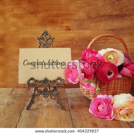 pink flowers in the basket next to card with phrase: congratulations, on wooden table.  - stock photo