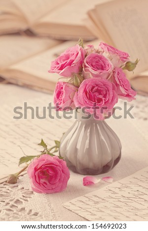 Pink flowers, letters and old books - stock photo