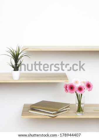 pink flowers on book shelf - stock photo