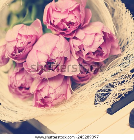 Pink flowers on piano holidays card - stock photo