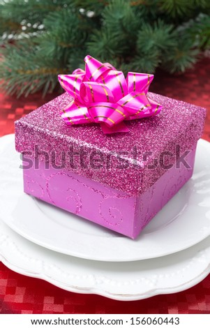Pink gift box on a plate for Christmas, close-up - stock photo