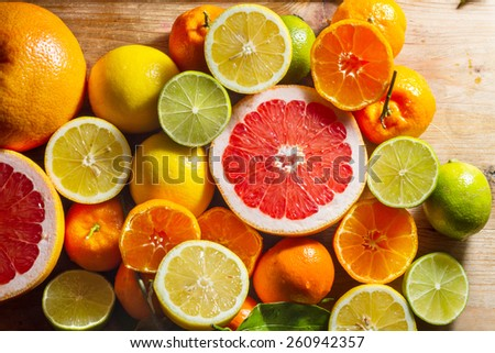 Pink grapefruit and other citrus fruit against wooden background. - stock photo