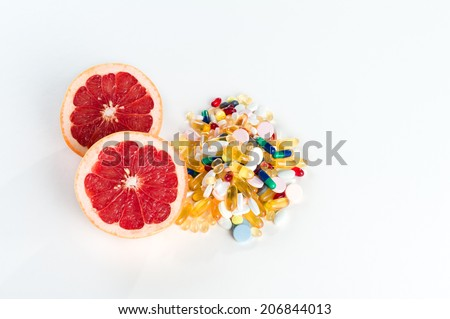Pink grapefruit and pills, vitamin supplements on white background with copy space, healthy diet concept - stock photo