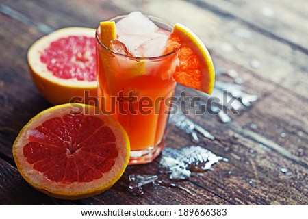 Pink grapefruit drinks with crushed ice on wooden background - stock photo