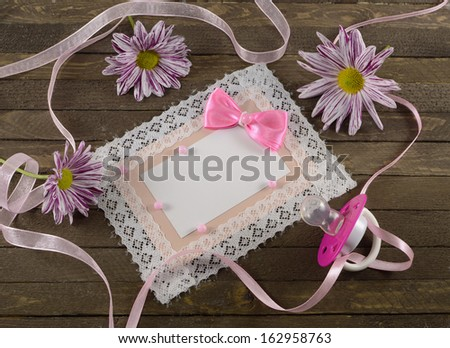 Pink greeting card with pacifier on wooden planks - stock photo