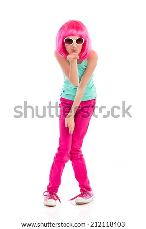 Pink haired little girl in sunglasses blowing a kiss. Full length studio shot isolated on white. - stock photo