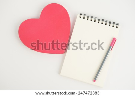 Pink Heart gift box and notebook pen on white background - stock photo