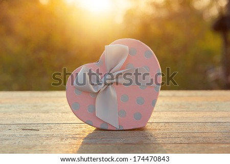 Pink Heart gift box on wood table  in sunset - stock photo