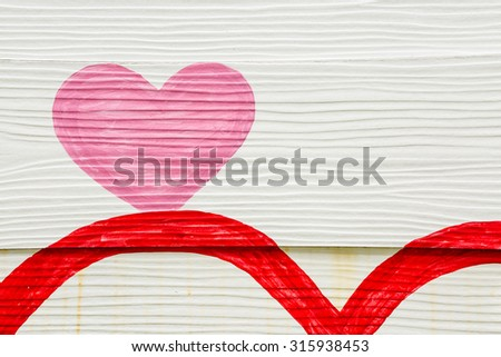 Pink heart painted on white wooden wall - stock photo