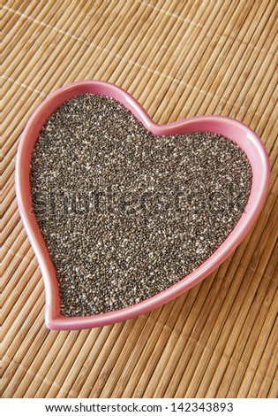 Pink heart shaped dish of chia seeds - stock photo