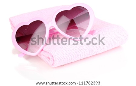 Pink heart-shaped sunglasses on towel isolated on white - stock photo