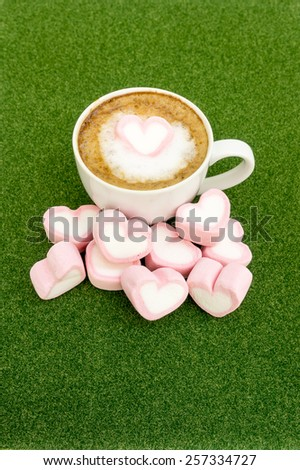 Pink hearts marshmallow on latte cofee for valentines green grass background. - stock photo