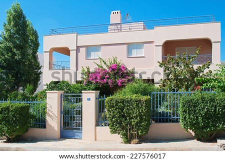 Pink house with a fence and flowering trees on a street in the city Saronida in Greece. - stock photo