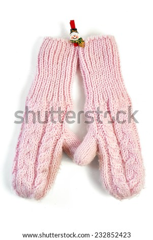 Pink knitted mittens on clothespin-snowman on white background - stock photo