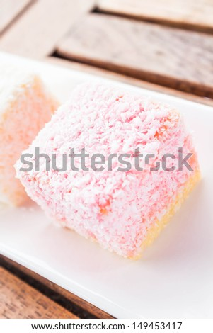 Pink lamington cakes up close on wood table, stock photo - stock photo