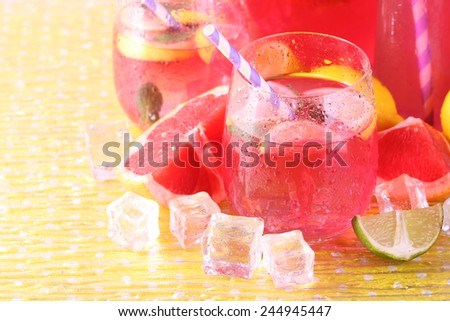 Pink lemonade in glasses and pitcher on bright background - stock photo