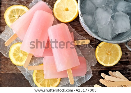 Pink lemonade popsicles with ice pail and lemon slices on a rustic wood background - stock photo