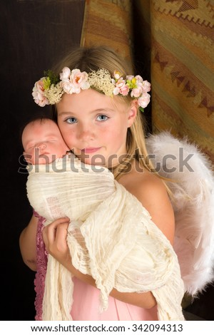 Pink little girl playing an angel in a Christmas nativity scene (the baby is a doll) - stock photo